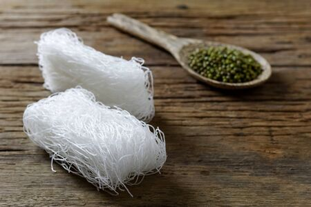 Dry Glass Noodle (Transparent bean vermicelli) on wood plate with Green beans on spoon