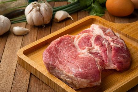 Raw pork shoulder on wooden plate background.