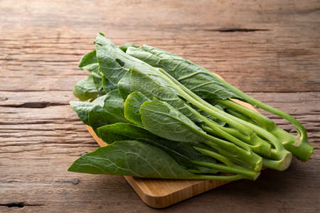 Close up Chinese kale vegetable on wooden plate Stock Photo
