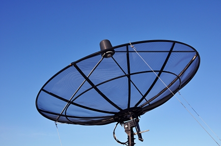 A satellite dish on blue sky background photo
