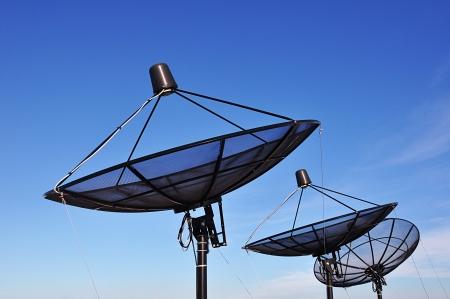 Satellite dishes on blue sky background photo