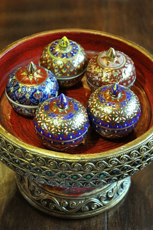 Ancient thai style porcelain containers on a carving wooden base photo