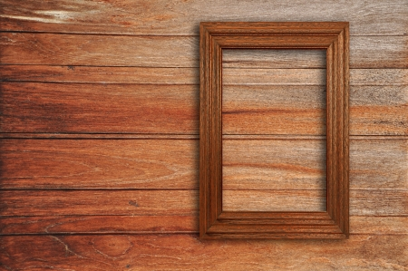 Wooden picture frame on old wooden wall photo