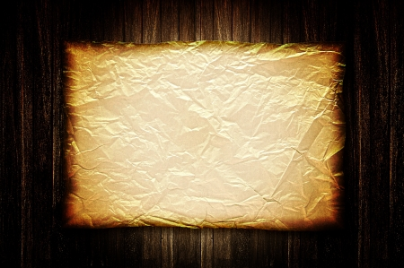 burnt wood: Burnt old crumpled paper on wood background Stock Photo