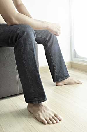 Man wearing jeans sitting on stool photo