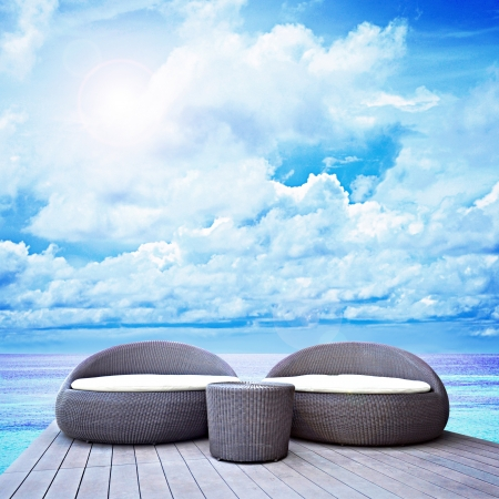 luxury hotel: Relaxing rattan lounge  above beautiful blue sea Stock Photo