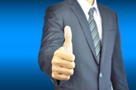 Businessman giving thumb up on blue background photo