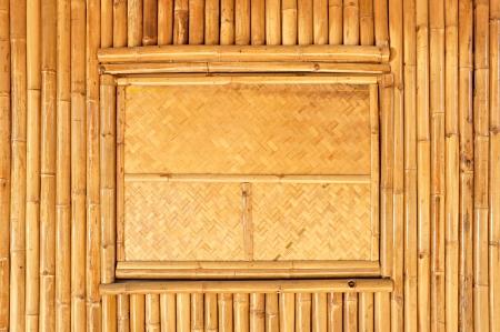 Woven window panel on bamboo wall photo