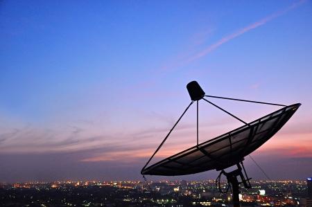 antena parabolica: Una antena parab�lica sobre la ciudad Foto de archivo