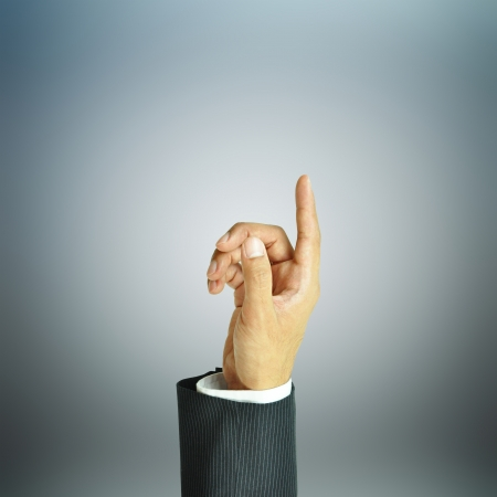 Businessman hand pointing up on gray background photo