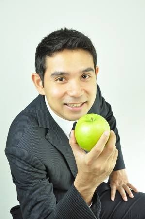 Smiling businessman holding green apple photo