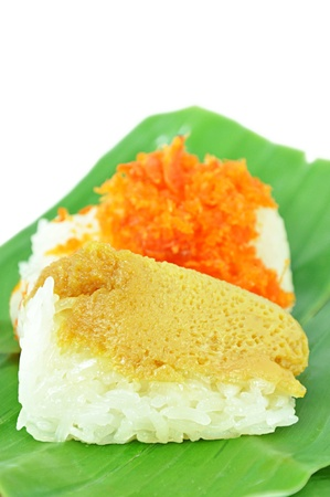 Traditional Thai dessert - sweet sticky rice top with steamed egg custard and minced coconut, shrimp on banana leaf photo