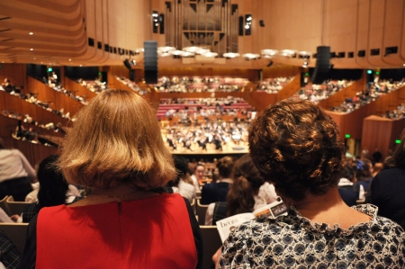 behind the scenes: People watching symphony orchestra performing in the concert hall