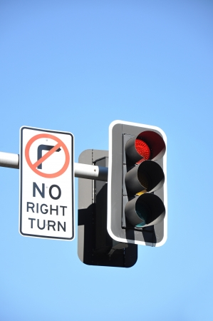 Traffic light and NO RIGHT TURN sign on blue sky background photo