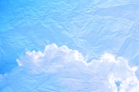 Blue sky and cloud picture on wrinkled paper photo