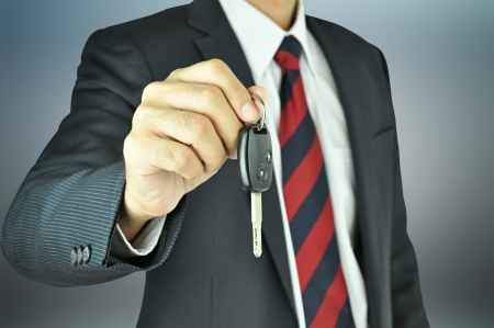 sell car: Businessman giving a car key Stock Photo