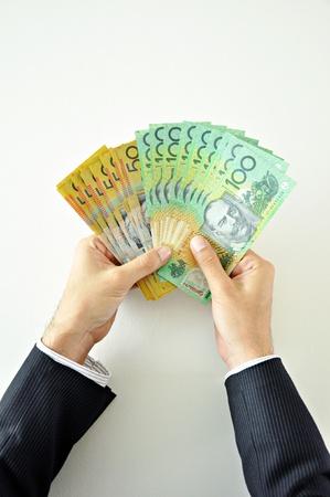 australian money: Businessman hands holding money - Australian Dollar banknotes