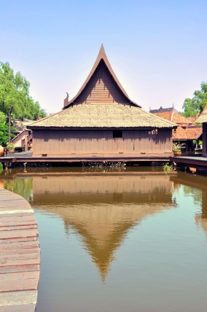 Ancient Thai style wooden houses above the pond - Floating village photo
