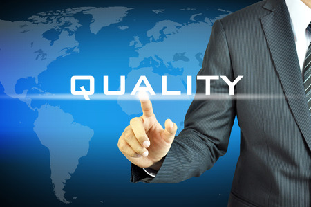 qc: Businessman touching  QUALITY sign on virtual screen Stock Photo