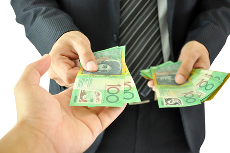 Businessman hand giving money  - Australian dollars