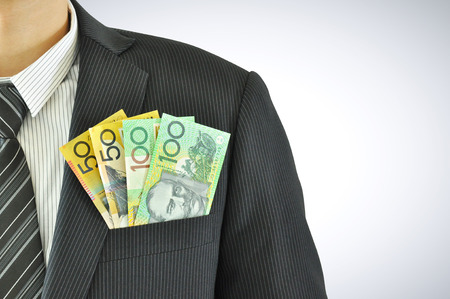 Money in businessman pocket suit - AUD - Australian Dollars Stock Photo