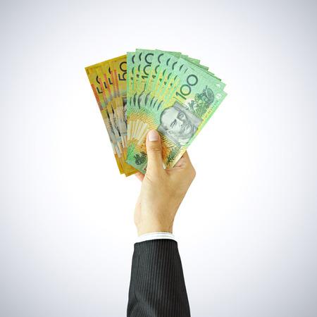 australian money: Hand giving money - AUD - Australian Dollars