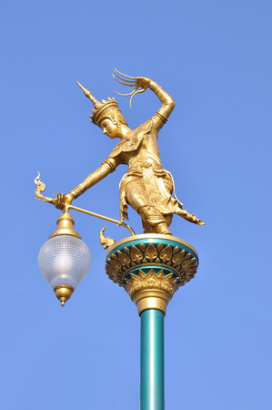 legendary: Ancient Thai style street lamp - golden woman statue as legendary character performing ancient Thai dance Stock Photo