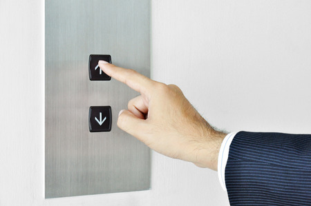 Businessman hand touching going up sign on lift control panel photo