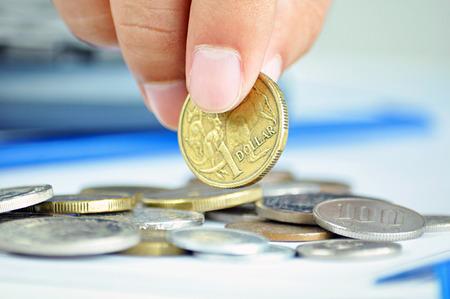 australian money: Fingers picking up a coin - one Australian dollar (AUD) Stock Photo