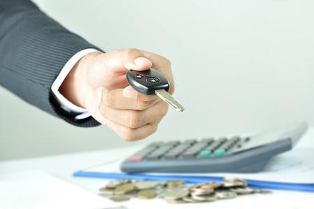 Businessman hand giving a car key - car rent, sale & pawn concept photo