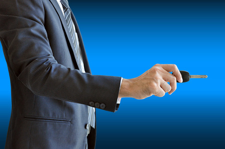 Businessman hand holding a car key on blue background photo