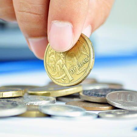 australian dollars: Fingers picking up a coin - one Australian dollar (AUD) Stock Photo