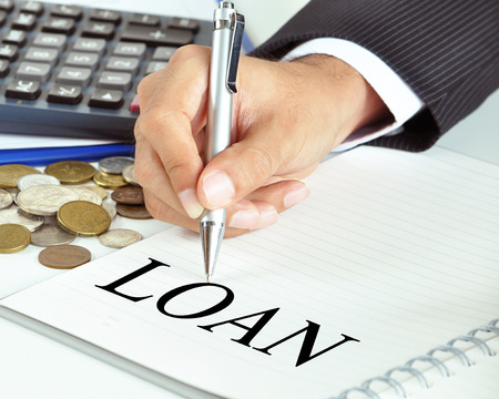 lend a hand: Hand with pen pointing to LOAN word on the paper - financial & business concept Stock Photo