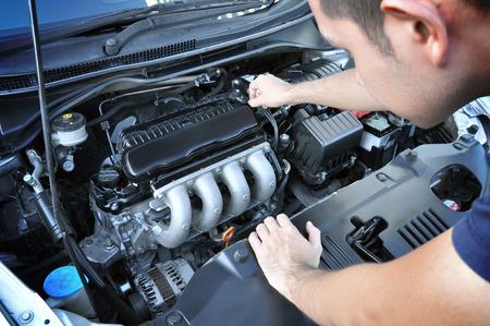 Een man het controleren van auto-motor