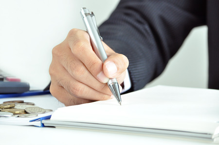 Businessman hand holding a pen writing on the book - business   financial concept photo