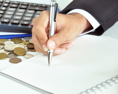 Businessman hand holding a pen writing on empty paper with coins   calculator aside - business   financial concept