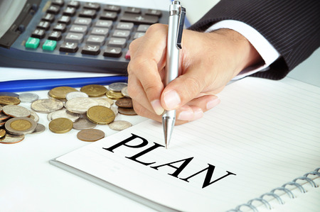 conspire: Hand with pen pointing to PLAN word on the paper  - business & financial concept