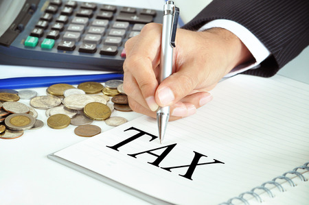 Businessman hand holding a pen pointing to TAX word on the paper - business & investment concept photo