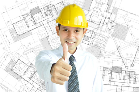 Smiling Asian engineer (or architect ) with yellow hard hat giving thumbs up on architectural sketch background