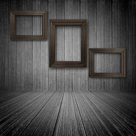 Three wooden picture frames on the wall inside dark room photo