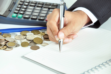 jot: Businessman hand holding a pen writing on empty paper with coins   calculator aside - business   financial concept