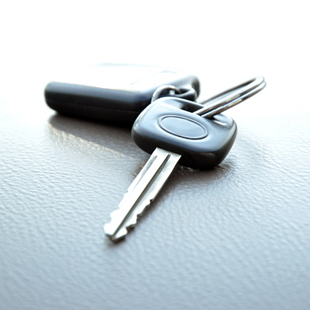 Car key with remote control key ring on gray leather texture photo