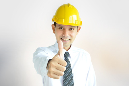 asian architect: Smiling Asian engineer (or architect ) with yellow hard hat giving thumbs up Stock Photo