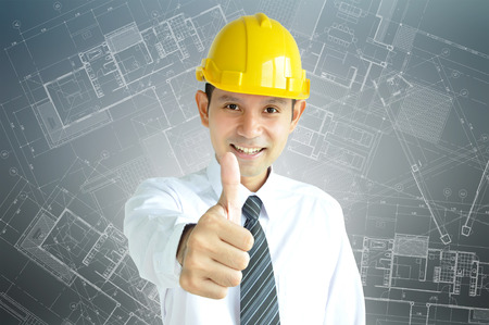 asian architect: Smiling Asian engineer (or architect ) with yellow hard hat giving thumbs up on gray architectural sketch background