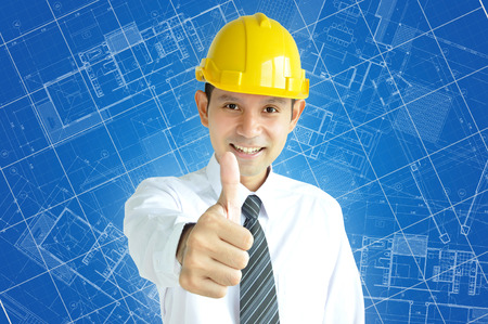 asian architect: Smiling Asian engineer (or architect ) with yellow hard hat giving thumbs up on blue architectural sketch background