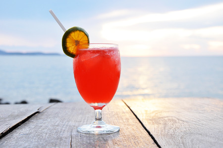mocktail: Cocktail drink with orange slice as a garnish on old wooden table and sea water  Stock Photo