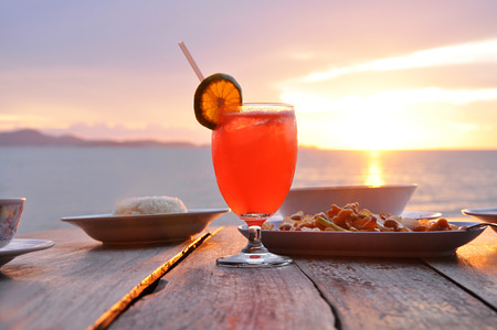 Cocktail drink with some Asian foods on old wooden table and sea water