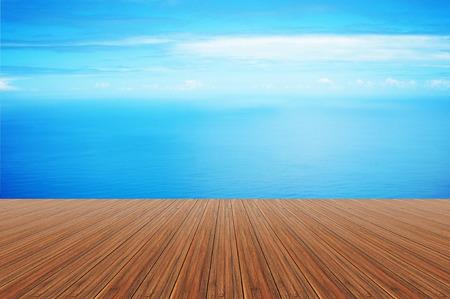 still water: Wood plank on still blue sea water and sky