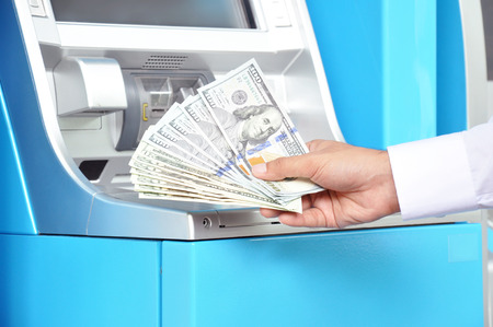 automatic teller machine bank: Money - hand holding US dollar banknotes in front of ATM