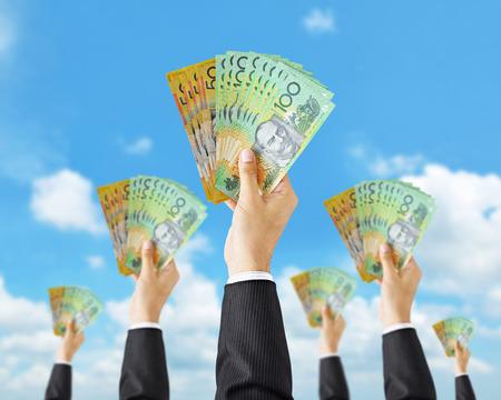 australian dollar notes: Hands holding money - Australian dollar (AUD) banknotes - money raising, funding & consumerism concept